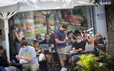 Israelis, some wearing protective face masks and some not, at a cafe in Tel Aviv on June 16, 2020. (Miriam Alster/Flash90)