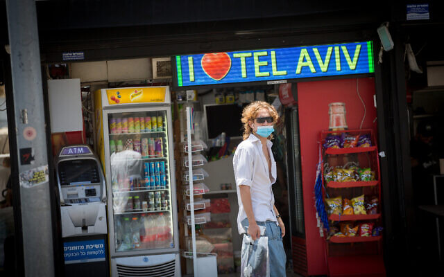 Israelis wear protective face masks  in Tel Aviv on June 16, 2020. (Miriam Alster/Flash90)