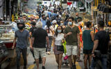 Illustrative: Israelis, wearing facemasks for fear of the coronavirus, shop for groceries at the Mahane Yehuda market in Jerusalem after it reopened according to the new government orders, June 16, 2020. (Olivier Fitoussi/Flash90)