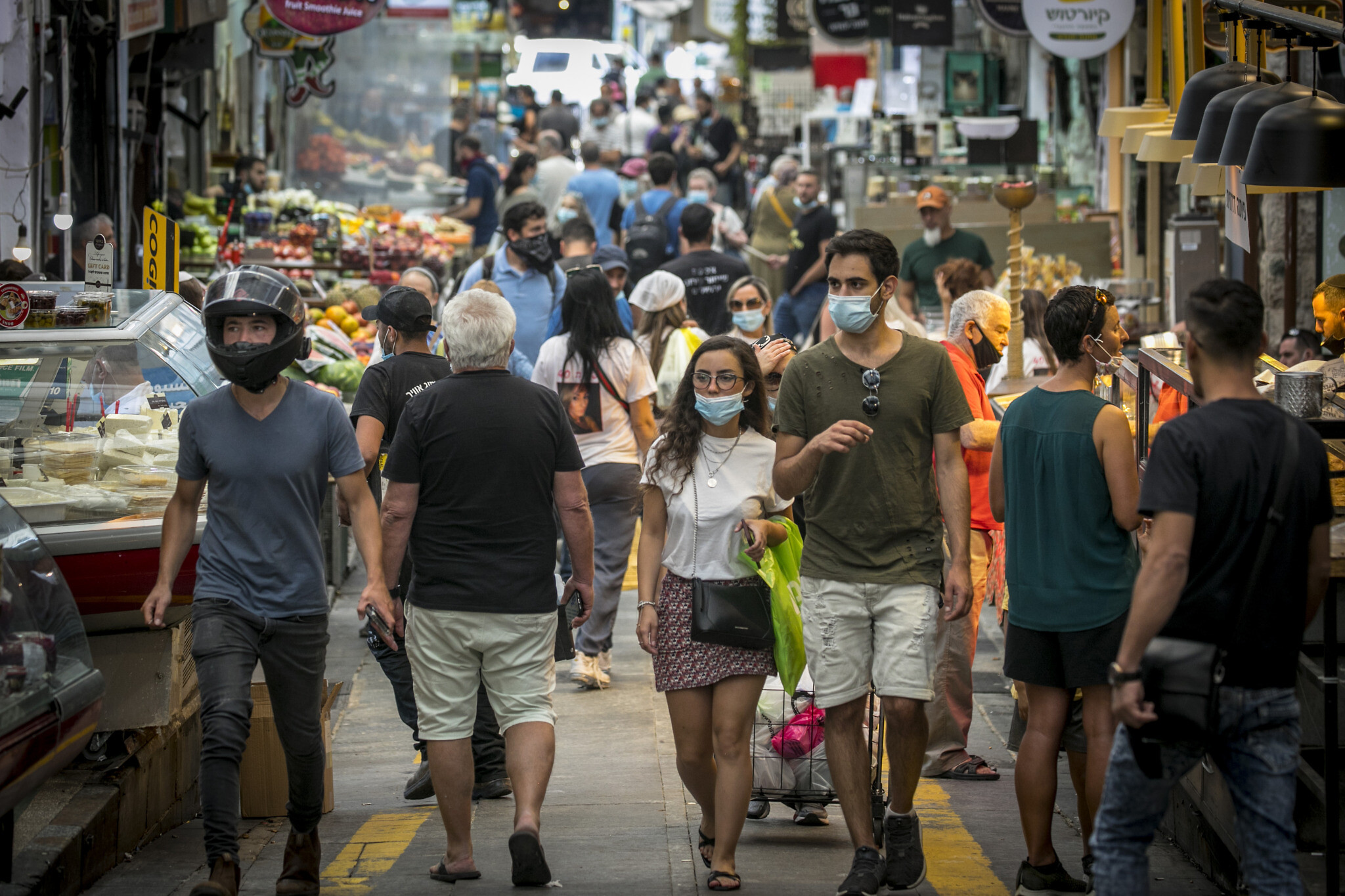Israelis, wearing facemasks for fear of the coronavirus, shop for groceries at the Mahane Yehuda market in Jerusalem after it reopened according to the new government orders, June 16, 2020. (Olivier Fitoussi/Flash90)