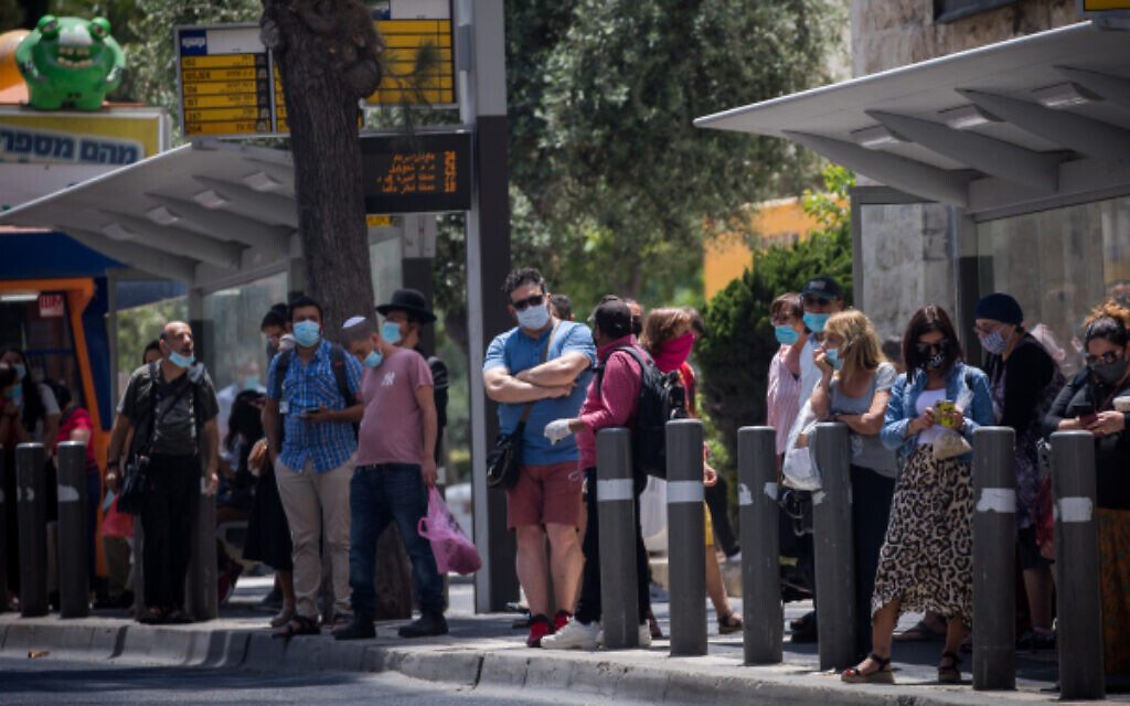 People with face masks wait for a bus at a bus stop in downtown Jerusalem on June 18, 2020 (Yonatan Sindel/Flash90)