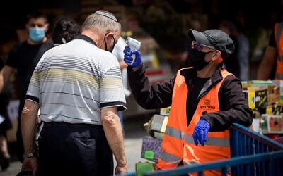 A man checks the temperature of a customer at the entrance to the Mahane Yehuda Market in Jerusalem on June 18, 2020. (Yonatan Sindel/Flash90)