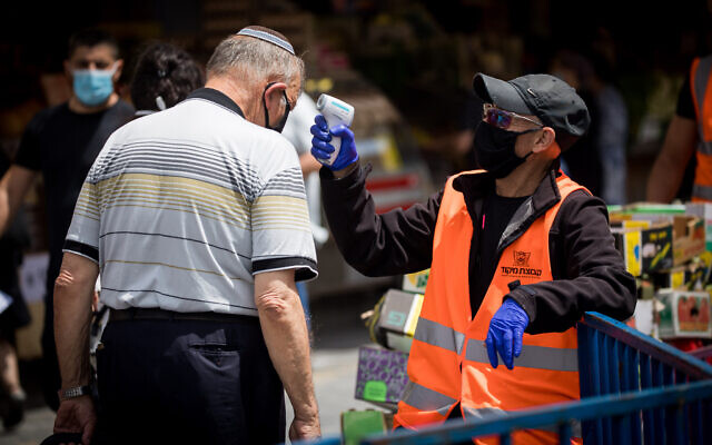 A man checks the temperature of a customer at the entrance to the Mahane Yehuda Market in Jerusalem on June 18, 2020. (Yonatan Sindel/Flash90)