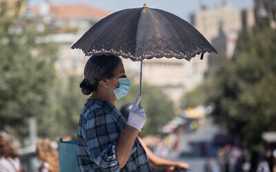 People walk with face masks on Jaffa Street in downtown Jerusalem on June 24, 2020. (Yonatan Sindel/Flash90)