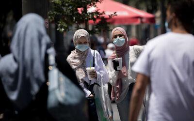 People walk with face masks on Jaffa Street in downtown Jerusalem on June 25, 2020. (Yonatan Sindel/Flash90)