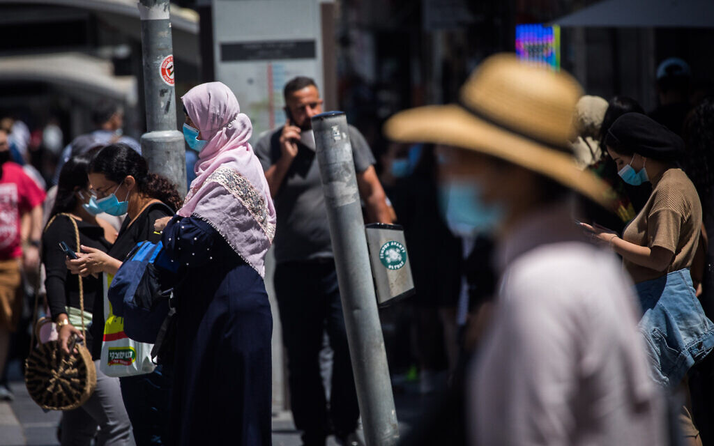 People walk with face masks on Jaffa Street in downtown Jerusalem on June 25, 2020. (Yonatan Sindel/Flash90)