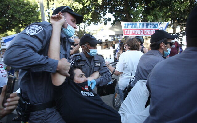 Police remove a protester during a protest against Prime Minister Benjamin Netanyahu outside the Prime Minister's Residence in Jerusalem, June 26, 2020. (Yonatan Sindel/Flash90)