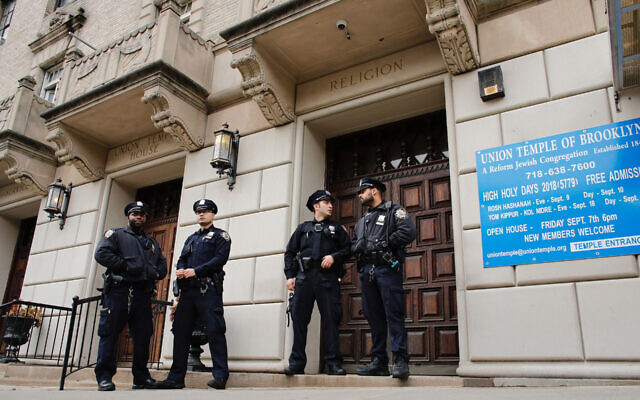 Illustrative: New York police officers stand guard at the door of the Union Temple of Brooklyn after it was vandalized with graffiti, November 2, 2018. (Kena Betancur/AFP via Getty Images)