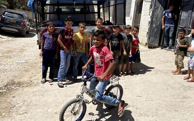 Children pose for a photo in the Jordan Valley Palestinian village of Fasa'il on June 10, 2020. (Jacob Magid/Times of Israel)