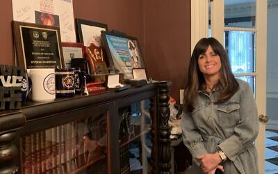Devorah Halberstam in front of the many commendations and awards she's received from local, state and federal law enforcement. (Cathryn J. Prince/Times of Israel)