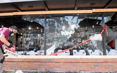 Workers repair a damaged storefront on Fairfax Avenue on May 31, 2020 in Los Angeles, California. (Valerie Macon/AFP)