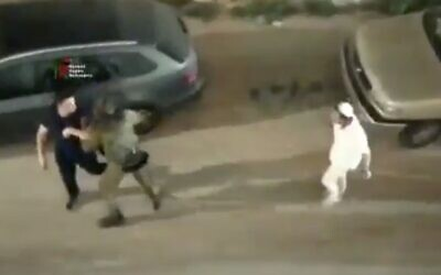 An IDF soldier (center) helps a Palestinian man (left) flee from a group of Israelis attacking him in the West Bank city of Hebron on June 13, 2020. (Screen capture: Twitter)