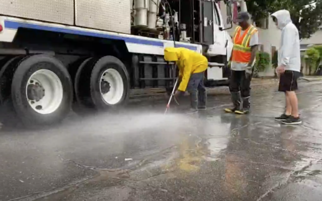 Screen capture from video of city workers cleaning anti-Semitic graffiti from the road outside the Gates of Prayer Cemetery, New Orleans, June 8, 2020. (WWL-TV)