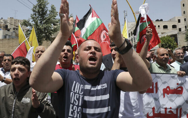 FILE: Palestinian supporters of the Fatah movement demonstrate in the West Bank city of Hebron, June 5, 2020. (Hazem Bader/AFP)