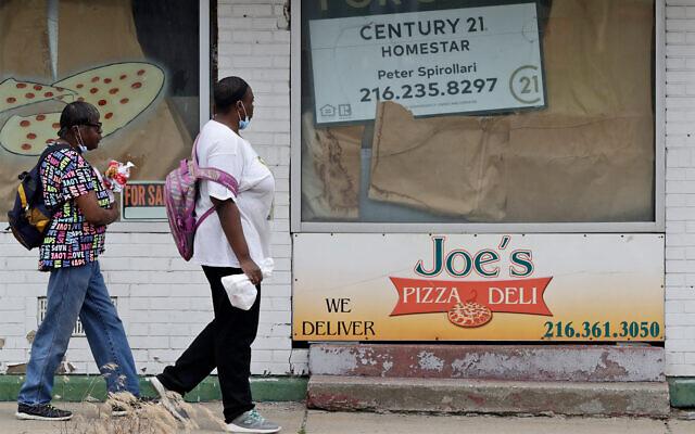 Two women walk past a closed pizza deli in Cleveland, Ohio, June 4, 2020. (AP/Tony Dejak)