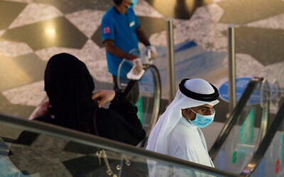 An Emirati man and woman ride an escalator at Mall of the Emirates in Dubai, United Arab Emirates, as the country loosens its coronavirus restrictions, May 27, 2020. (AP Photo/Jon Gambrell)