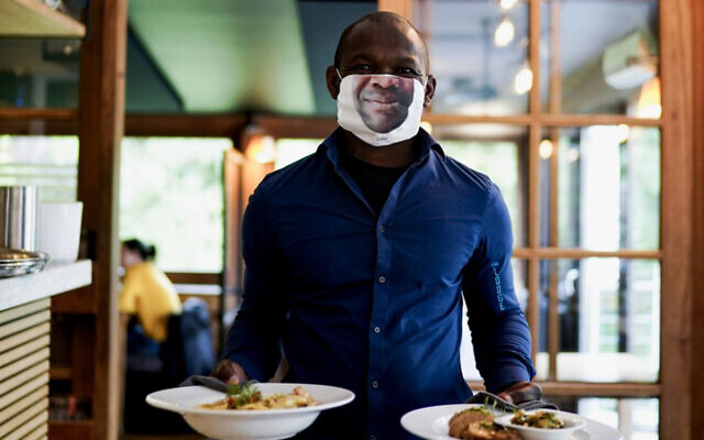 """A waiter wearing a protective face mask with a picture of his face, works at the """"Lodge"""" restaurant in Brussels, Belgium, June 8, 2020. (Kenzo Tribouillard/AFP)"""
