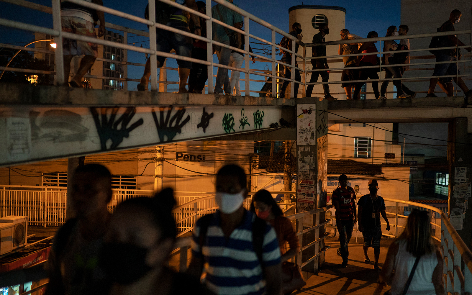 People, some wearing masks to curb the spread of the coronavirus, on a footbridge to a bus and train station in Rio de Janeiro, Brazil, June 25, 2020. (AP Photo/Leo Correa)