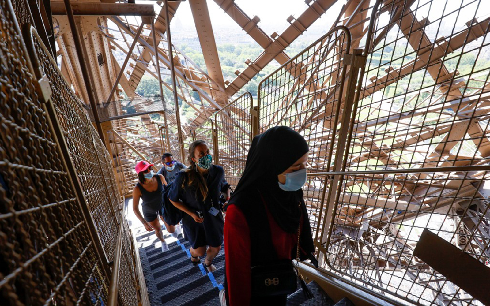 Visitors wearing protective masks walk up the stairs of the Eiffel Tower during its partial reopening in Paris, June 25, 2020. (Thomas Samson/AFP)