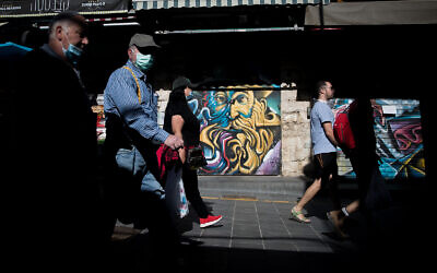 People walk past closed stores in the Mahane Yehuda market in Jerusalem, May 4, 2020. (Yonatan Sindel/Flash90)