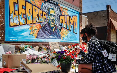 Malaysia Hammond, 19, places flowers at a memorial mural for George Floyd at the corner of Chicago Avenue and 38th Street, May 31, 2020, in Minneapolis. (AP/John Minchillo)