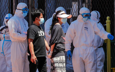 Workers in protective suits direct people to get a virus test at a stadium in Beijing, June 14, 2020. (AP/Andy Wong)