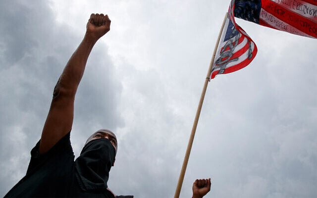A demonstrator holds a fist in the air next to a American flag with the names of Black people who have been killed by police as people demonstrate by the Lincoln Memorial on Juneteenth in Washington, June 19, 2020. (AP/Jacquelyn Martin)