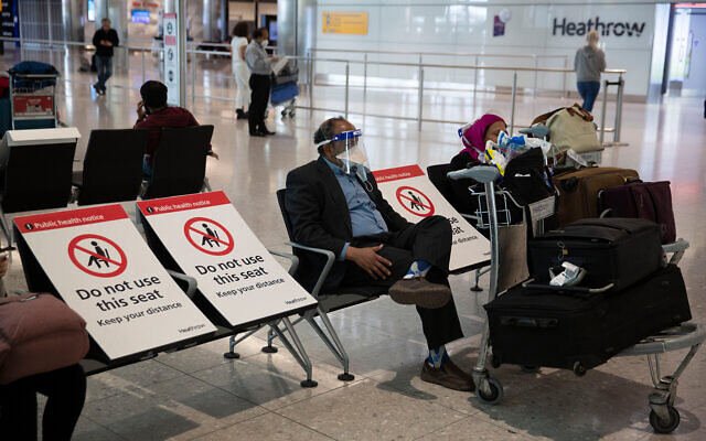 A man sits wearing a face shield in the arrivals area on the first day of new rules mandating arrivals to Britain to quarantine themselves for 14 days to help stop the spread of coronavirus, at Heathrow Airpot in London, June 8, 2020. (AP/Matt Dunham)