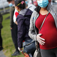 A pregnant woman wearing a face mask and gloves holds her belly as she waits in line for groceries in Waltham, Massachusetts, May 7, 2020. (AP Photo/Charles Krupa)