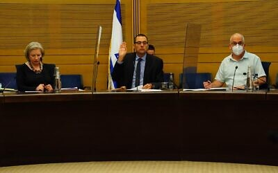 The Knesset's Foreign Affairs and Defense Committee chairman Zvi Hauser (center) votes on a bill that would allow the Shin Bet to use tracking technology to identify those exposed to the coronavirus, on June 30, 2020. (Adena Welman/Knesset)