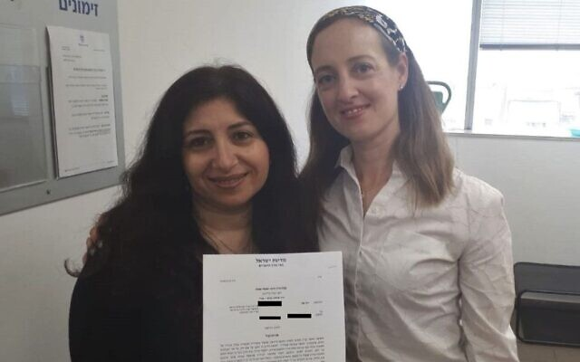 Vicly Tzur, left holds her writ of divorce with Tamar Oderberg of Yad La'isha, after a 14-year battle to obtain a get from her husband, undated. (Courtesy of Ohr Torah Stone via JTA)