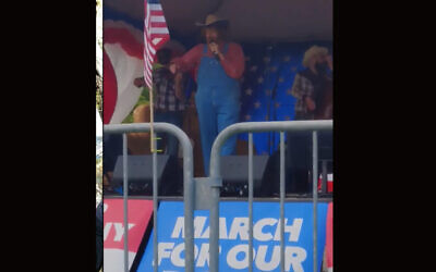 Comedian Sacha Baron Cohen performs a song with racist and conspiracy theory-laden lyrics at a far-right rally in Olympia, Washington, June 27, 2020. (Screenshot from YouTube)