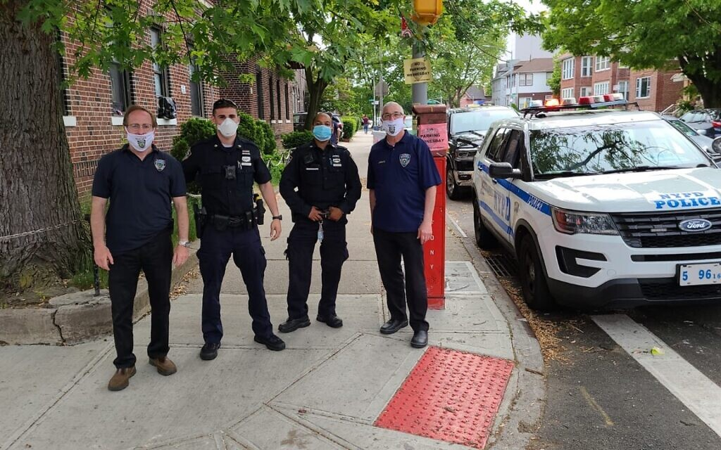 Executive coordinator for the Flatbush Shomrim Safety Patrol Bob Moskovitz, left, stands with NYPD officers in Flatbush, Brooklyn. (Courtesy)