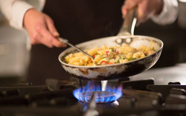 Illustrative: A cook prepares a dish on a stove. (iStock by Getty Images)