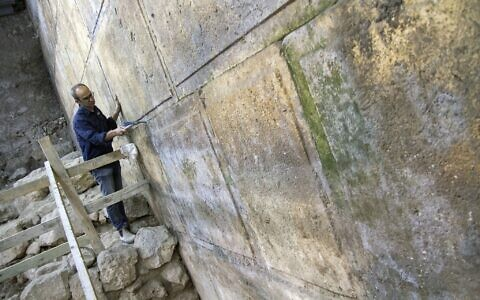Archaeologist Joe Uziel cleans the newly uncovered Western Wall courses, located under Wilson's Arch in the Jerusalem Old City. October 2017. (Yaniv Berman/Israel Antiquities Authority)