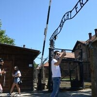 Visitors walk below the gate with its inscription 'Work sets you free' as the memorial site of the former German Nazi death camp Auschwitz in Oswiecim, Poland reopens on July 1, 2020. (BARTOSZ SIEDLIK / AFP)