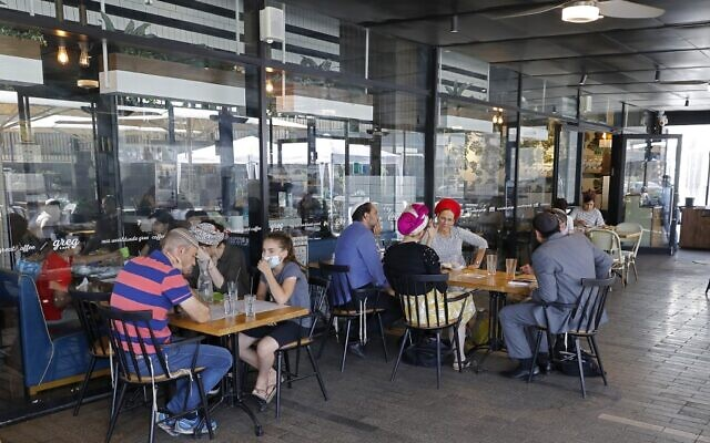 Israeli sit at a cafe in the West Bank settlement of Ariel, on July 1, 2020. (Jack Guez/AFP)