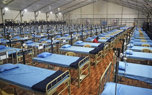 A man sits next to beds at a newly built hospital to treat Covid-19 coronavirus patients at the Mahalaxmi Racecourse, in Mumbai on July 7, 2020. (Punit PARANJPE / AFP)