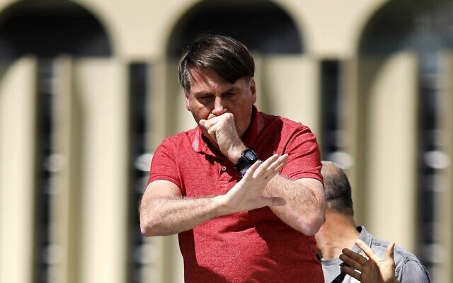 Brazilian President Jair Bolsonaro coughs as he speaks after joining supporters who were taking part in a motorcade to protest against quarantine and social distancing measures against the coronavirus outbreak, on April 19, 2020, in Brasilia. (Sergio Lima/AFP)