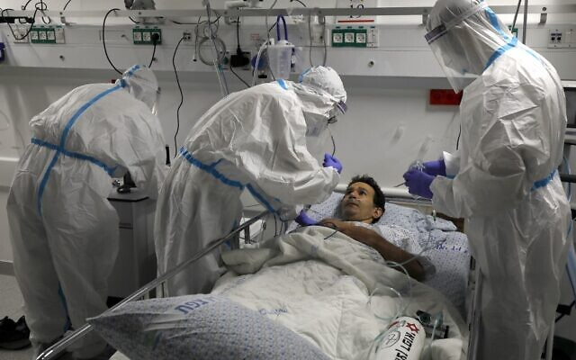 Medical workers simulate treatment for covid-19 on a volunteer during a training session on July 9, 2020, as the coronavirus ward at Ziv Medical Center in the northern city of Safed prepares to reopen. (Jalaa Marey/AFP)