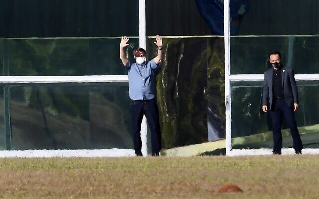 Brazilian President Jair Bolsonaro waves outside Alvorada Palace in Brasilia on July 9, 2020. (Photo by EVARISTO SA / AFP)