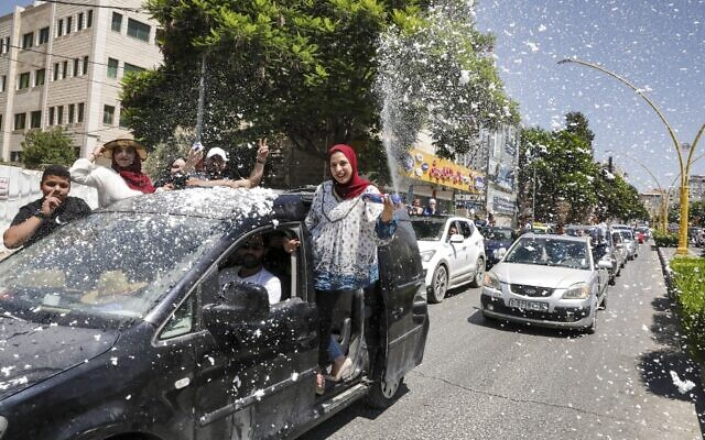 Palestinian high school students wave and spray artificial snow from a moving vehicle as they celebrate the announcement of their matriculation exams in Hebron in the West Bank on July 11, 2020. (HAZEM BADER / AFP)
