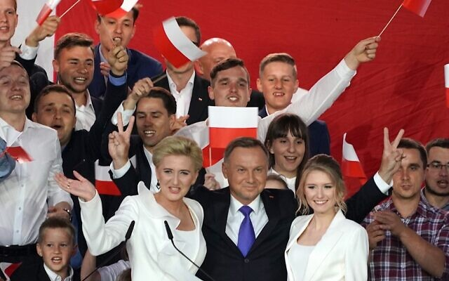 Polish President Andrzej Duda flashes V-signs after addressing supporters with his wife Agata (L) as exit poll results were announced during the presidential election in Pultusk, Poland, on July 12, 2020 (JANEK SKARZYNSKI / AFP)