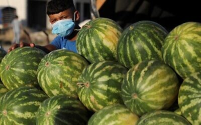 A mask-clad child sells watermelons in the Askar refugee camp, east of the West Bank city of Nablus, amid the novel coronavirus pandemic crisis, on July 13, 2020. ( JAAFAR ASHTIYEH / AFP)