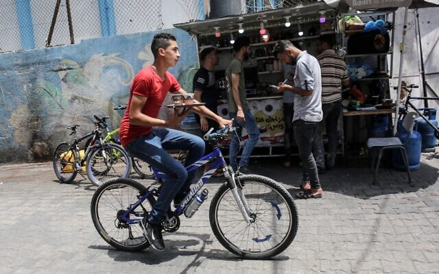 A delivery employee carries a tray of steaming cups of coffee in front of Shaaban Hamuda's  small stand near Rafah market, in the southern Gaza Strip, on July 13, 2020. (SAID KHATIB / AFP)