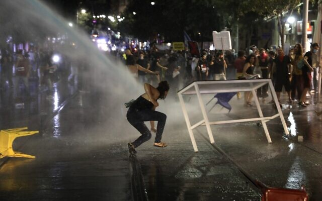 A protester slips as Israeli police use water cannons during clashes at a demonstration against Prime Minister  Benjamin Netanyahu in Jerusalem, on July 14, 2020. (MENAHEM KAHANA / AFP)