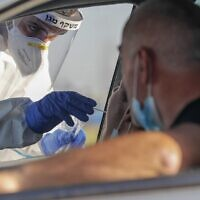 A Magen David Adom paramedic swabs a person for COVID-19 at a drive-thru testing site in the central city of Lod on July 15, 2020. (Ahmad Gharabli/AFP)