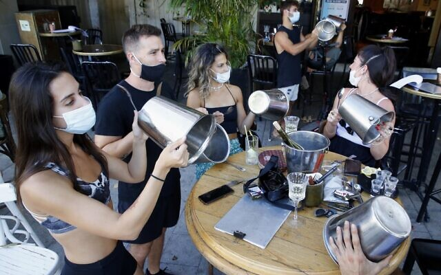 Illustrative: Mask-clad Israeli restaurant owners and others protest against lockdown measures in Tel Aviv on July 17, 2020. (JACK GUEZ / AFP)