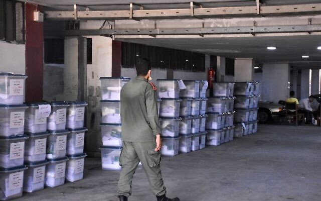 A Syrian policeman walks past ballot boxes, ahead of handing them over to the police to deliver them to polling stations on the eve of the parliamentary elections, in the Syrian city of Aleppo on July 18, 2020 (AFP)