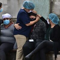 Relatives and friends of Honduran journalist David Romero, the head of Globo radio and TV station who was sentenced in 2019 to nearly 11 years in prison for defamation, cry after he died of complications from COVID-19 during the novel coronavirus pandemic, in Tegucigalpa, on July 18, 2020. (Orlando SIERRA / AFP)